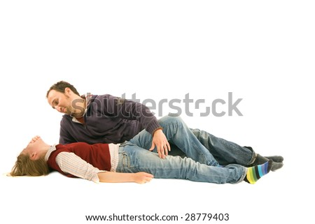 A man is lying near his girl. He looks at her while she is laughing. - stock photo