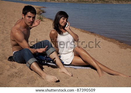 a man is not happy that his girlfriend is on the phone while they are on vacation. - stock photo