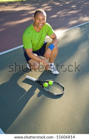 A man is outside on a tennis court.  He is crouching down and smiling at the camera.  Vertically framed shot.