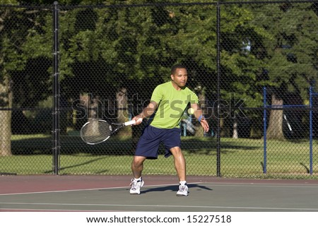 A man is outside on a tennis court playing tennis.  He is looking at the tennis ball, and he is about to hit it with his racket.  Horizontally framed shot.