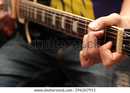 a man is playing on guitar