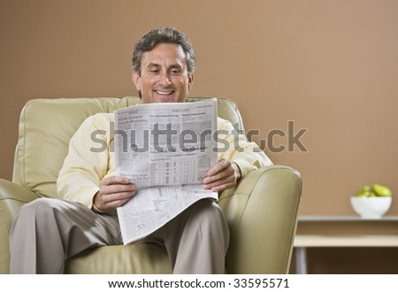 A man is reading a newspaper.  He is smiling and looking down at the paper.  Horizontally framed shot.