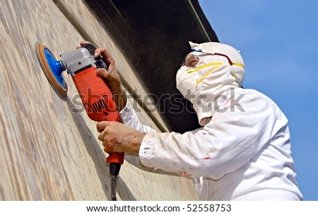 A man  is sanding a building gable with a rotary grinder. He is dressed in protective clothing plus mask and goggles to protect himself from the cloud of sawdust being generated. - stock photo