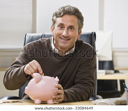 A man is seated at a desk in an office and is putting a coin into a piggy bank.  He is smiling at the camera.  Horizontally framed shot. - stock photo