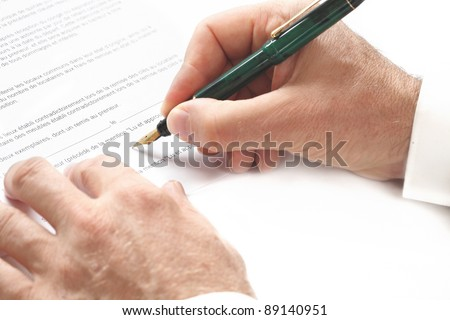 A man is signing a contract with a pen - stock photo