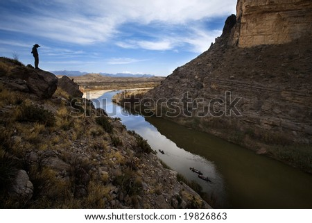 A man is silhouetted in Santa Elena canyon as he looks down at three canoes in the Rio Grande, Big Bend National Park, Texas.  The left side of the river is the United States, on the right is Mexico. - stock photo