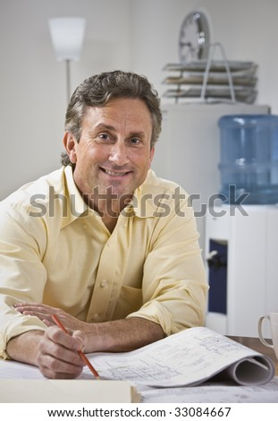 A man is sitting at a desk and working on blueprints.  He is smiling at the camera.  Vertically framed shot.