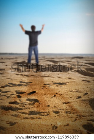 A man is standing on a beach with sand and has his hands held up in happiness, freedom or faith. - stock photo