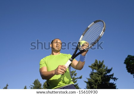 A man is standing outside on a tennis court.  He is holding a tennis racket, about to serve the ball, and looking away from the camera.  Horizontally framed shot. - stock photo