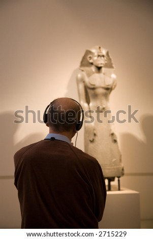 a man is taking part a guided tour of a museum - stock photo