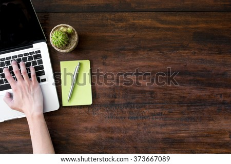 A man is using a laptop on old wood office desk table with laptop, green notebook and pen. Top view with copy space. - stock photo