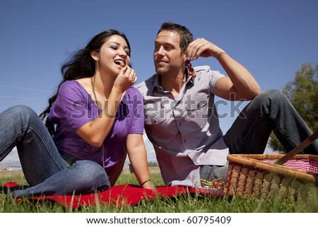 A man is watching a woman eating some grapes - stock photo