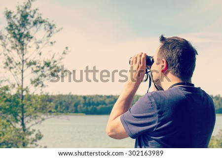 A man is watching birds and scenery with binoculars from high above the ground. The sea or lake is on the background. Image has a vintage effect applied. - stock photo