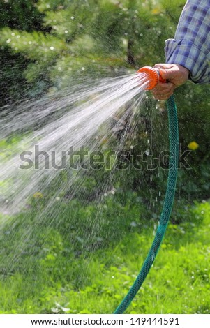 a man is watering grass - stock photo