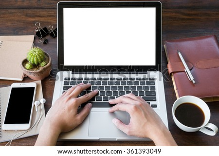A man is working by using a laptop computer on vintage wooden table. Hand typing on a keyboard. Front view. - stock photo