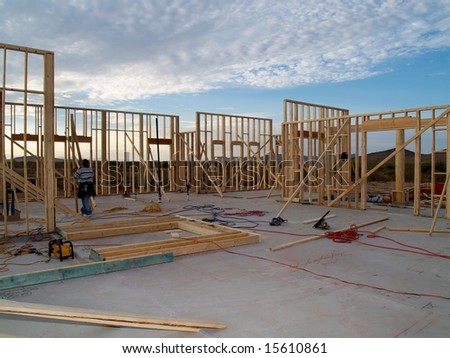 A man is working on building a wall of a house.  He is looking at his work with his back facing the camera.  Horizontally framed shot.