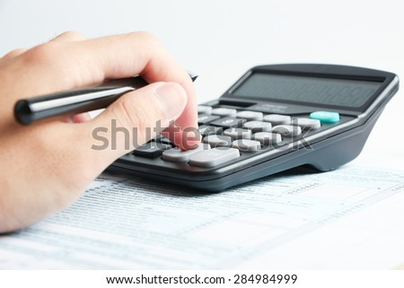 A man is working with a calculator in office.