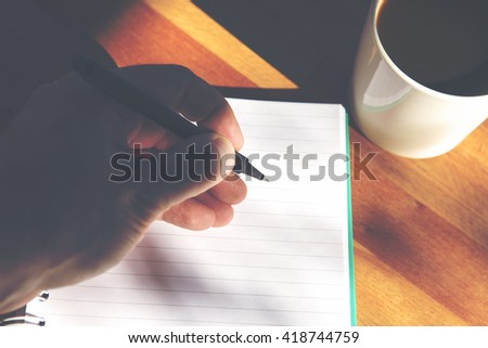 A man is writing a letter. A cup of coffee is next to the empty notepad page. Image has a vintage effect applied. - stock photo