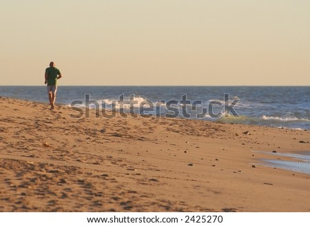 A man jogging on a California beach on an overcast winter day. - stock photo