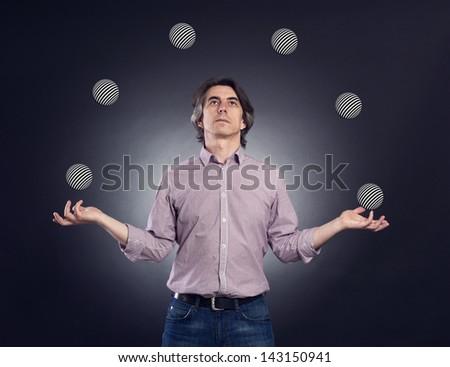 A man juggling several balls. - stock photo