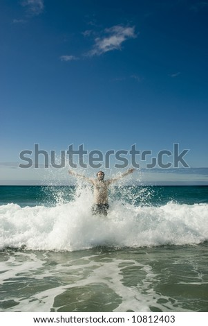 a man jumping a wave in the beach