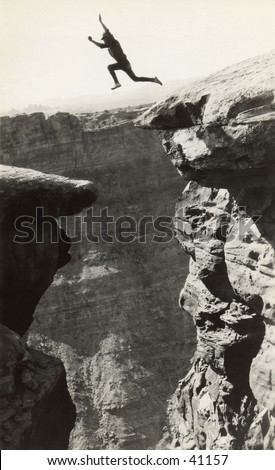 A man jumping from one ledge to another in the Grand Canyon. A circa 1900, vintage photograph.