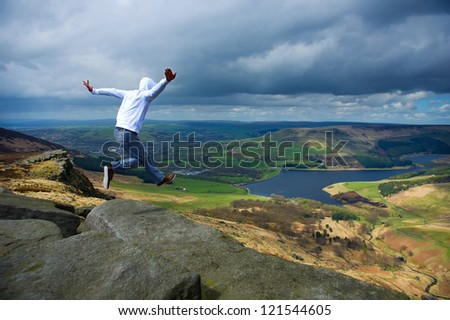 A man jumping off a cliff - stock photo