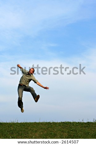 A man jumping playfully against a blue sky over green grass
