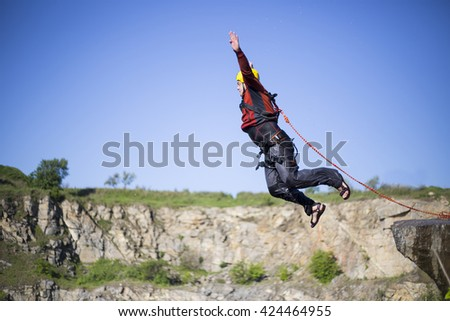 A man jumps from a cliff into the abyss. - stock photo