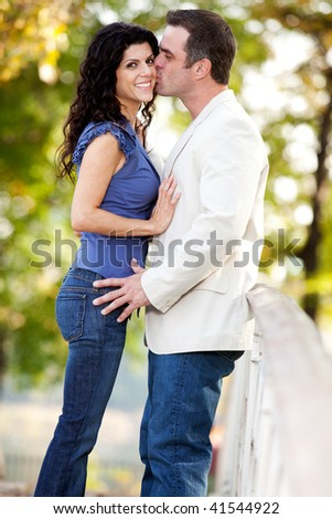 A man kissing a woman on the cheek in a park - stock photo
