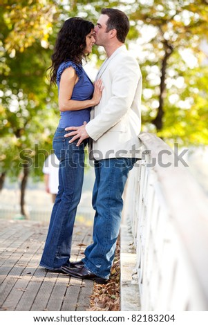 A man kissing a woman on the forehead - stock photo
