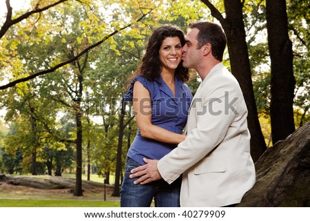 A man kissing his girlfriend / wife in the park - stock photo