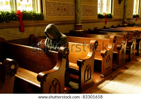 A man kneeling and praying at a church at Christmas time. - stock photo
