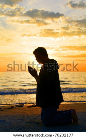 A man kneeling and praying at the ocean with the sun framing his head. - stock photo