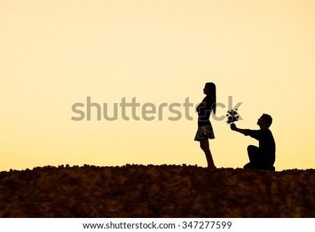 A man kneeling down begging for love - stock photo