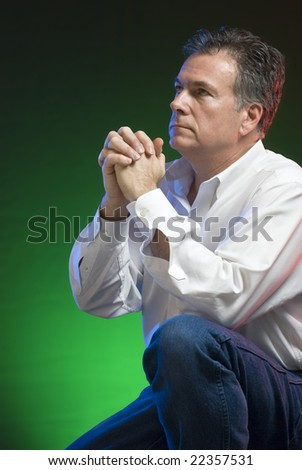 A man kneeling in prayer, with green, blue and red gels applied for creative lighting. - stock photo