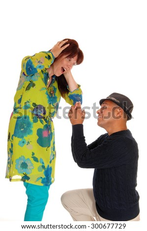 A man kneeling on the floor holding up a ring and proposing to his
