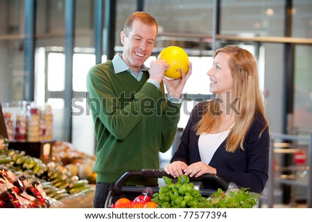 A man knocking on a melon to check if it is ripe - stock photo