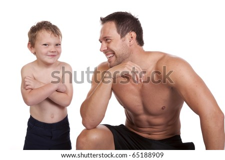 A man laughing at how his son is standing with a smirk on his face showing off their  muscles.