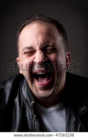 A man laughing hysterically at something hilarious with a funny expression on his face. - stock photo