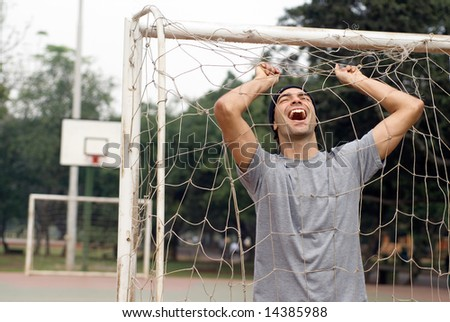 A man, laughing while holding onto a soccer goal net, standing. - horizontally framed - stock photo