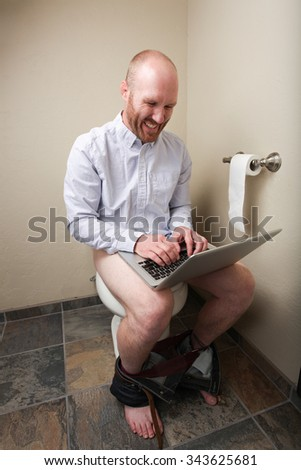 A man laughing while using his computer on the toilet - stock photo