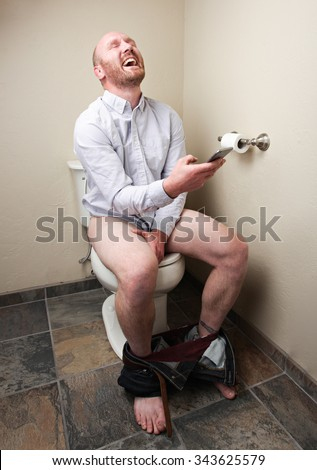 A man laughting while looking at his phone while on the toilet - stock photo