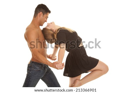 A man leaning his woman into his chest while dancing. - stock photo