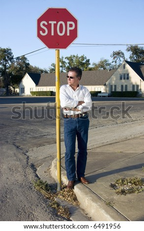 A man leaning leisurely against a stop sign at the corner of a quite intersection. - stock photo