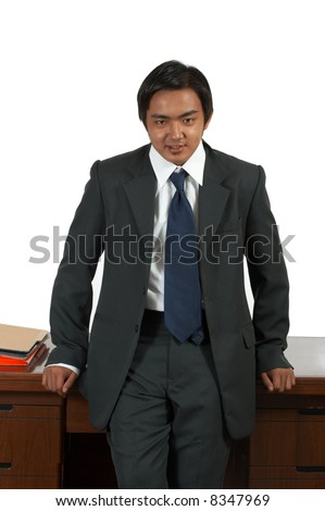 a man leaning on an office desk - stock photo