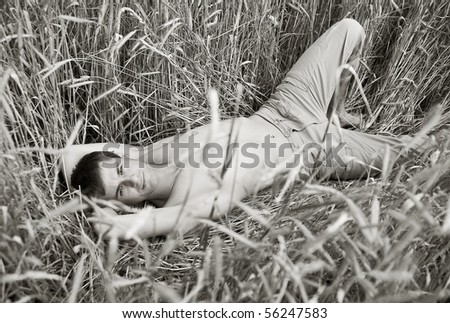 A man lie in field of wheat. black-and-white photo - stock photo