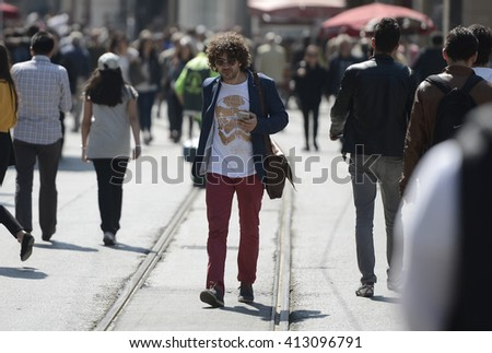 A man listening music  while walking on Istiklal street in Istanbul, Turkey, 28 April 2016 - stock photo