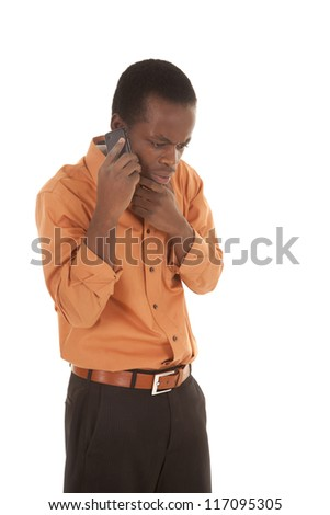 A man listening on his cell phone with a upset expression on his face - stock photo