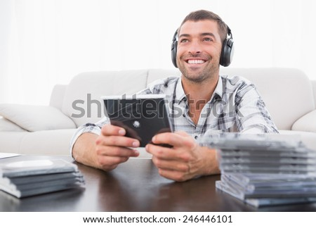 A man listening to cds at home in the living room - stock photo